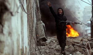 A Free Syrian Army fighter in front of a burning barricade in Damascus