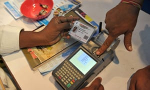 An Indian man gives a thumb impression to withdraw money from his bank account with his Aadhaar card in Hyderabad.