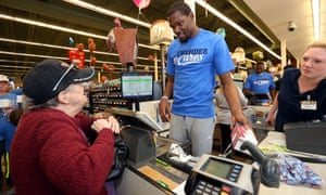 Kevin Durant works the checkout register during a  community service event in 2015