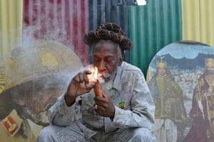 Bunny Wailer enjoys a smoke in a yard in Kingston, Jamaica in 2014