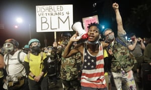 A demonstrator shouts slogans using a bullhorn next to a group of military veterans during a Black Lives Matter protest in Portland.