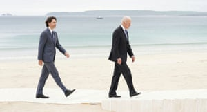 Canada's prime minister Justin Trudeau walks along the boardwalk with Biden during the G7 summit
