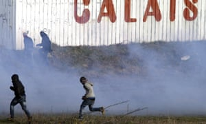Migrants run away from tear gas thrown by police forces near the Channel tunnel in Calais.