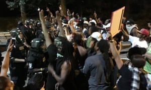 Protestors demonstrate in front of police officers wearing riot gear after police fatally shot Keith Lamont Scott in the parking lot of an apartment complex in Charlotte, North Carolina.