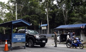 Malaysian anti-smuggling officers check on vehicles at the Malaysia-Thailand border