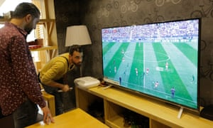 Football fans watch the opening game of 2018 World Cup between Russia and Saudi Arabia on the large-screen TV in Damascus.
