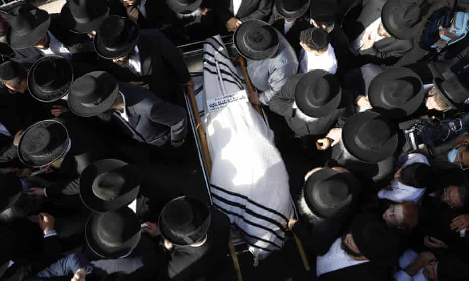 Body wrapped in a prayer shawl surrounded by mourners