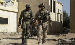 Armed men in uniform identified by Syrian Democratic forces as US special operations forces walk in the village of Fatisah in the northern Syrian province of Raqqa on Thursday.
