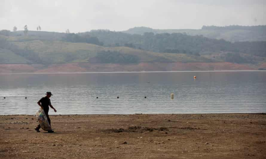 A man collects waste on the exposed banks of Lake Calima, Colombia. High temperatures due to El Niño have reduced the level of water in the reservoir.