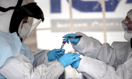 Health workers dressed in personal protective equipment (PPE) handle a coronavirus test at a drive-thru testing station at Cummings Park on March 23, 2020 in Stamford, Connecticut. Availability of protective clothing for medical workers has become a major issue as COVID-19 cases surge throughout the United States. The Stamford site is run by Murphy Medical Associates.