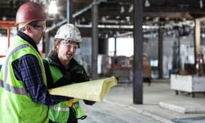 The gender pay gap is more prevalent in construction than in most industries.Two workers looking at blue prints in interior commercial building construction site