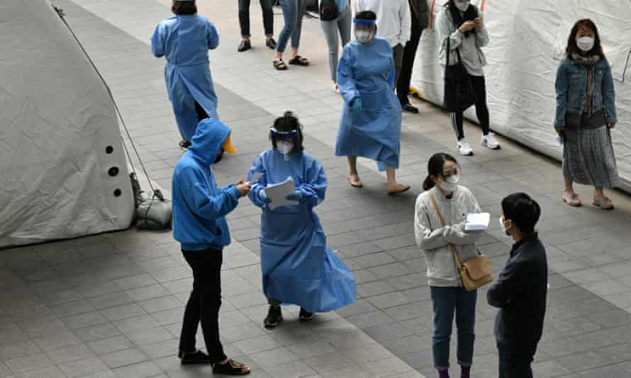 Medical staff deal with visitors waiting to be tested at a coronavirus testing station in Seoul, South Korea