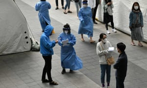 Medical staff members (in blue gowns) wearing protective clothing guide visitors at a virus testing station in the nightlife district of Itaewon in Seoul on 12 May 2020.