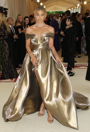 Model Jasmine Sanders aka Golden Barbie chose to make her MetGala debut wearing a bespoke liquid gold H&M gown, yet all eyes were on her waist-grazing braid pinned with tiny red roses.