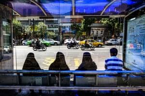 Women wait for a bus in Tehran, Iran