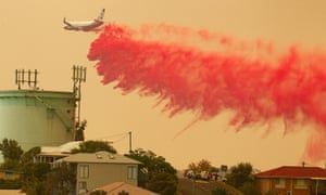 A water bombing plane drops fire retardant on a bushfire