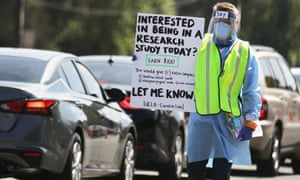 A worker carries a sign asking for participants to join a research study at a drive-in COVID-19 testing site amid the coronavirus pandemic on June 29, 2020 in Los Angeles, California.