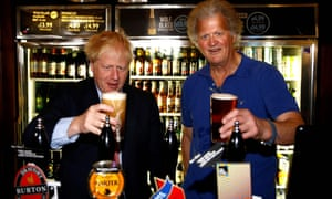 The new PM Boris Johnson poses with a pint of ale with JD Wetherspoon boss Tim Martin.