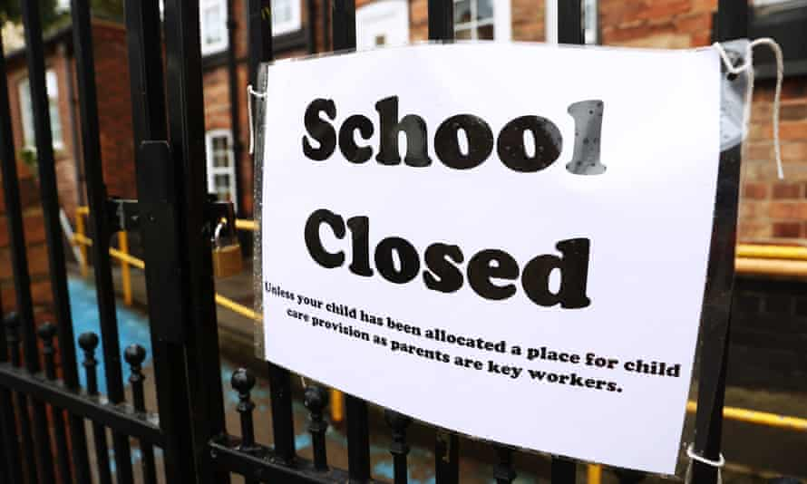 A sign is seen on the gates of a closed school.