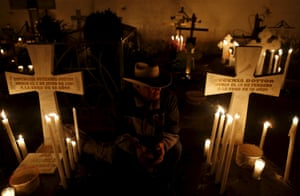 Mexico: A man sits next to the graves of relatives at a cemetery in Metepec