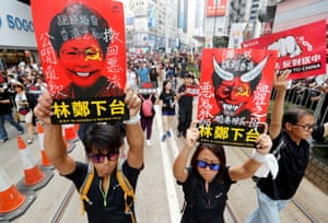 Protesters hold placards demanding Hong Kong's leaders step down