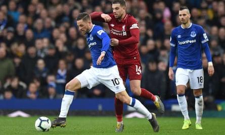 Everton's Gylfi Sigurdsson holds off Liverpool's Jordan Henderson.