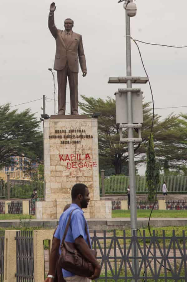 A man walks past a statue with a graffiti reading 'Kabila get out' in Kinshasa.