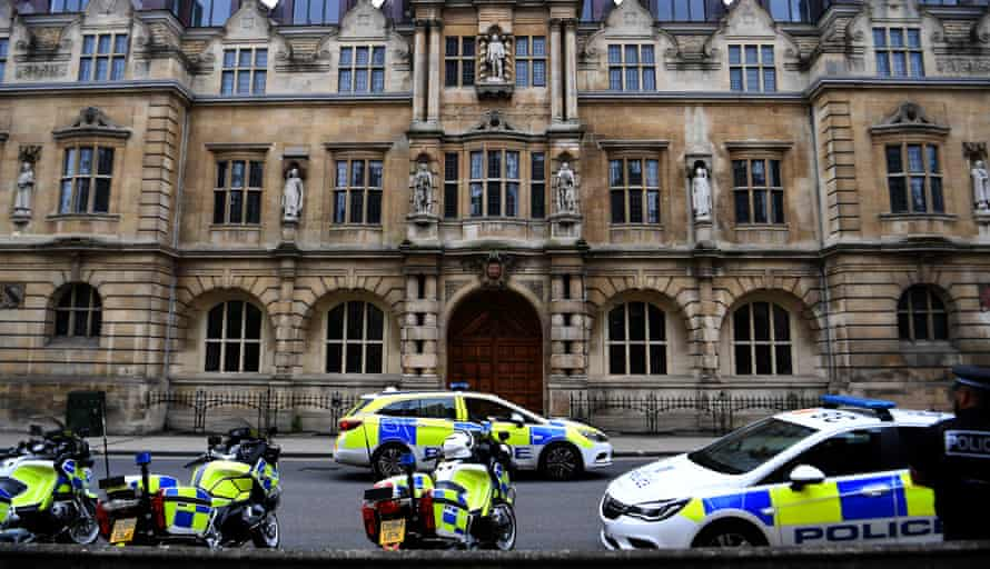 Police stand guard outside Cecil Rhodes statue on the facade of the Oriel College in Oxford, 12 June.