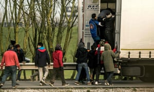 Migrants entering the trailer of a truck at the Eurotunnel site in Calais.