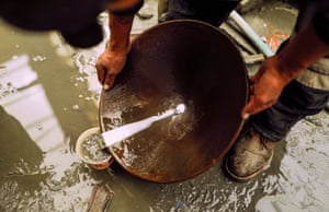 A miner uses a basin and mercury to pan for gold