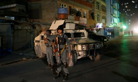 Afghan policemen stand guard near the site of an attack on the Shia shrine in Kabul