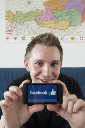 Max Schrems holds up a smartphone with the Facebook app on it.