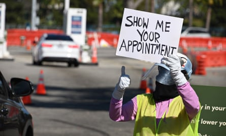 A worker gestures to an arriving car at a coronavirus testing site at Dodger Stadium in Los Angeles, California.