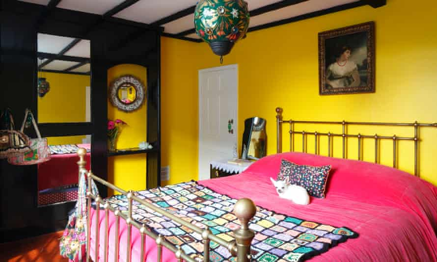 Pixie the dog on the bright pink cover on the bed in the 'liquorice allsorts' bedroom, with bright yellow walls and black woodwork