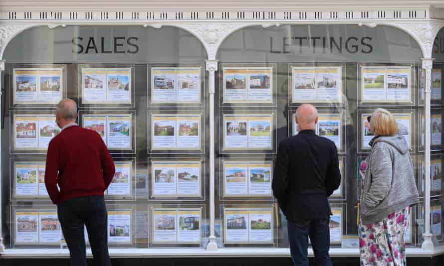 People looking at properties for sale in an estate agent's elegant (Victorian?) shop window