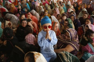 A child stands beside his mother at a ceremony in Lahore, Pakistan