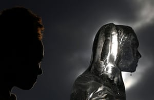 Water drips off an ice sculpture depicting a woman walking to collect water in London, UK, as part of a campaign by the charity WaterAid