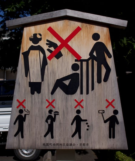 A sign in Kyoto cautions against touching geishas, taking selfies, littering, sitting on fences and eating and smoking on the street.