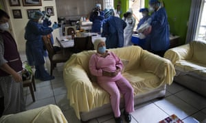 Rebeca Jimenez, 75, sits on a sofa in her home as journalists record health workers preparing to test her for Covid-19, in Mexico City, Wednesday, 17 June 2020.
