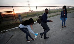 A teacher sanitizes the shoes of a student as schools begin to reopen in Cape Town, South Africa.