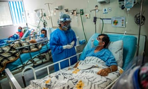 A health professional assists a Covid-19 patient in the Intensive Care Unit of the Alberto Sabogal Sologuren Hospital, in Lima, on December 11, 2020.