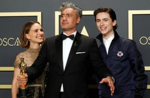 Taika Waititi, with his Oscar for best adapted screenplay for Jojo Rabbit, flanked by presenters Natalie Portman and Timothée Chalamet.