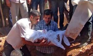 Alan Kurdi's father, Abdullah al-Kurdi, centre, holds his three-year-old son's body