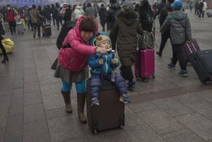 A Chinese woman pushes her child on a suitcase as they arrive for a train