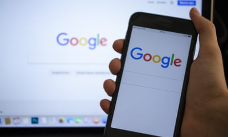 A Google logo on a phone screen and laptop.