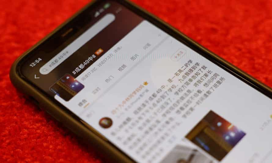 تلفن هوشمندی که پست Weibo را به زبان چینی و روی میز دراز کشیده نشان می دهد