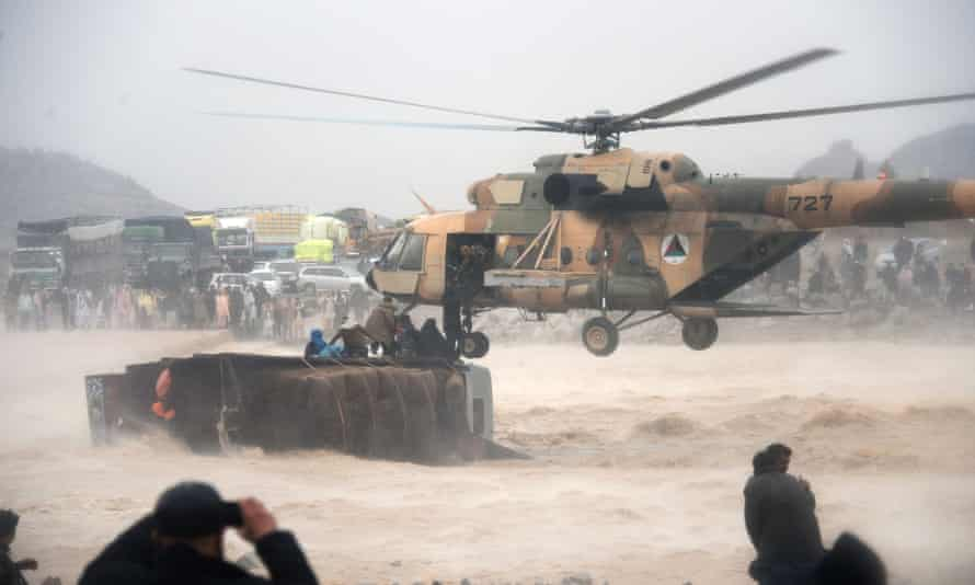 An Afghan military helicopter rescues people clinging to the top an overturned truck in flooded area of Arghandab district in Kandahar province.