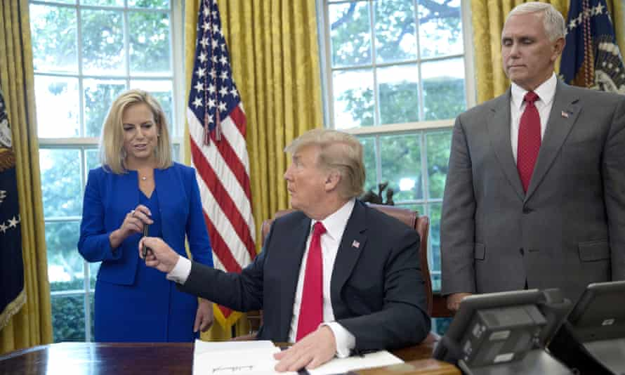Donald Trump signs the executive order to end family separations while watched by the DHS secretary, Kirstjen Nielsen, and the vice president, Mike Pence.
