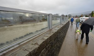 Residents walk by the recently constructed glass flood barrier which failed to stop the rising water in Keswick, northern England, on December 7, 2015.