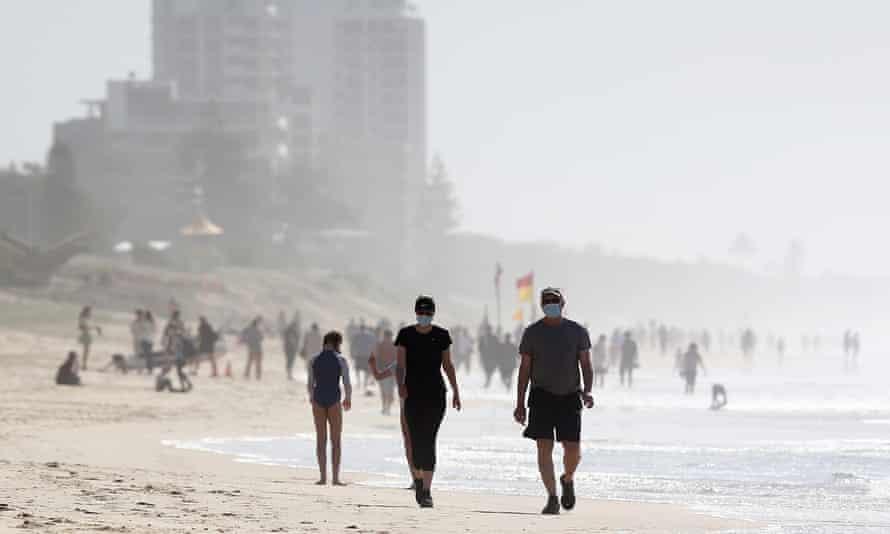 People walk along the beach at Surfers Paradise, Gold Coast, Australia,